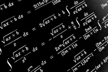 Large number of mathematical formulas on a black background Stock Photo