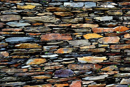 Close-up detail view of an old traditional stone wall built from schist in Piodão, made of shale rocks stack, one of Portugal's schist villages in the Aldeias do Xisto.