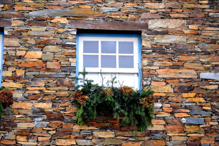Rustic hand-hewn wood window set into a stone wall built from schist in Piodão, made of shale rocks stack, one of Portugal's schist villages in the Aldeias do Xisto. Stock Photo