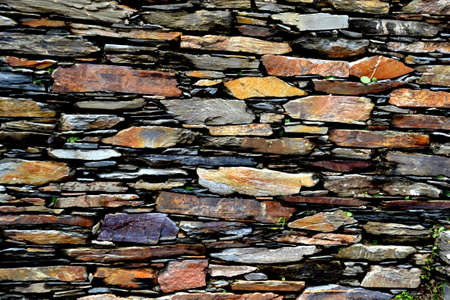 Close-up detail view of an old traditional stone wall built from schist in Piod�o, made of shale rocks stack, one of Portugal's schist villages in the Aldeias do Xisto. Stock Photo - 115002119