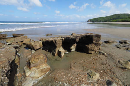 Playa El Coco, Nicaragua, on a sunny summer day showing its beach, rocks, vegetation and cloudscape. Imagens