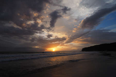 Sunset over the beach of Playa El Coco, Nicaragua, with a colorful cloudscape reflected in the coastal water. 免版税图像