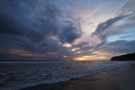 Sunset over the beach of Playa El Coco, Nicaragua, with a colorful cloudscape reflected in the coastal water. Imagens