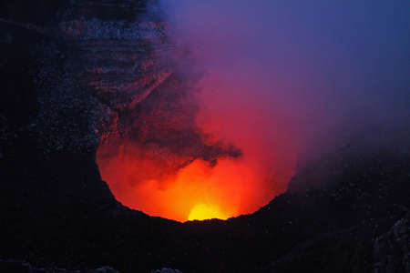 The active volcano in Masaya Volcano National Park, Masaya, Nicaragua, glowing red and yellow in the twilight. 스톡 콘텐츠