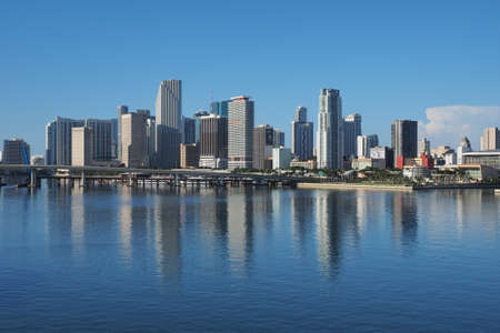 Miami, Florida 09-15-2018 The City of Miami skyline and its reflection on a very calm Biscayne Bay in morning light.