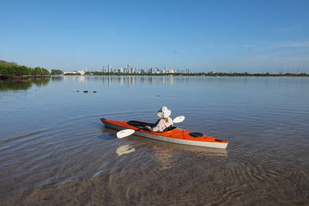 Key Biscayne, Florida 09-16-2017 Woman kayaks on very calm water in Bear Cut with the City of Miami skyline in the background.