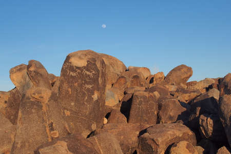 Petroglyphs attributed to the Hohokam people on Signal Hill in Saguaro National Park near Tucson, Arizona, with the rising moon in the background. Stock Photo
