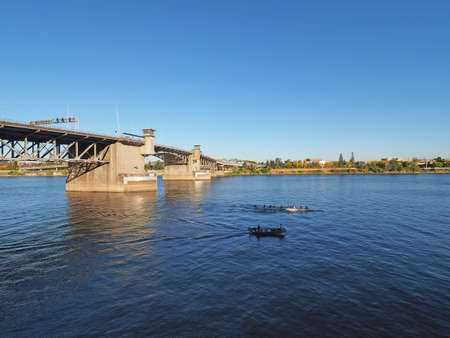 The Morrison Bridge over the Willamette River in Portland, Oregon, on a clear and cloudless autumn afternoon.