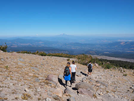 Hikers on the Timberline Trail on Mount Hood, Oregon, with distant views of Mount rainier and Mount Jefferson in the background on a very clear day. Stock Photo