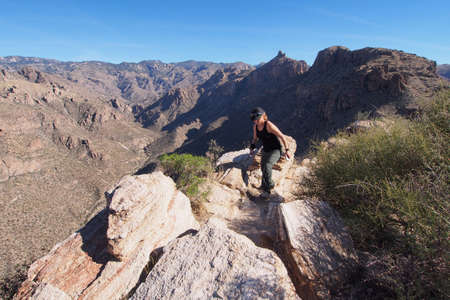 Woman enjoying expansive views at the end of the Blacketts Ridge Trail in the Santa Catalina Mountains near Tucson, Arizona.