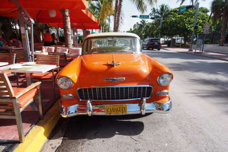 Miami Beach, Florida 08-17-2013 Beautifully restored orange and white antique Chevrolet sedan with Cuban license plate on Ocean Drive. Stockfoto - 118527617