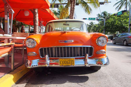 Miami Beach, Florida 08-17-2013 Beautifully restored orange and white antique Chevrolet sedan with Cuban license plate on Ocean Drive.