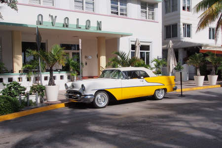 Miami Beach, Florida 08-17-2013 Restored antique yellow and white Oldsmobile convertible in front of the art deco Avalon Hotel on Ocean Drive.