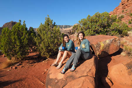 Two young sisters resting on a boulder on Horseshoe Mesa in Grand Canyon National Park, Arizona.