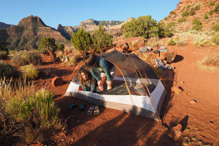 Two sisters sleepily emerging from their tent on Horseshoe Mesa in Grand Canyon National Park, Arizona.