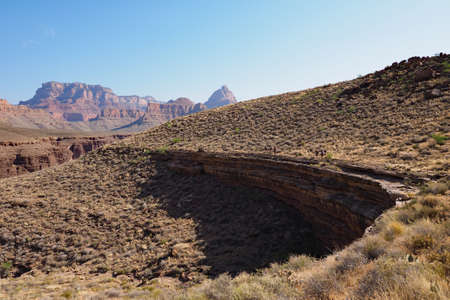 Distant backpackers on the Tonto Trail on a clear May morning in Grand Canyon National Park, Arizona.
