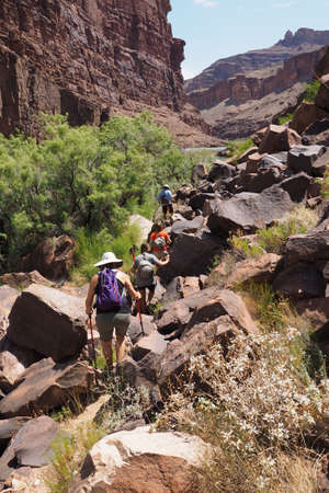 Hikers on a trail bordering the Colorado River above Hance Rapids in Grand Canyon National Park, Arizona.