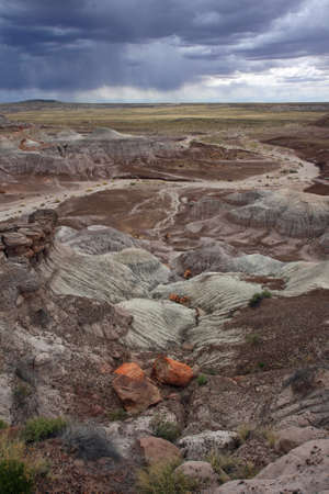 Badlands of the Painted Desert under a gathering rain storm in Petrified Forest National Park, Arizona.