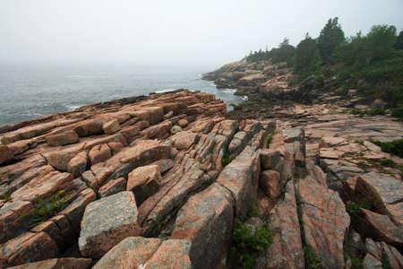 The rugged granite coast of Acadia National Park, Maine, on a foggy summer morning. Фото со стока
