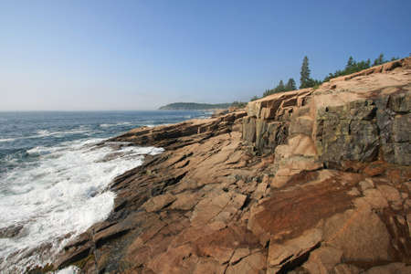 The rugged coast of Acadia National Park, Maine, on a sunny summer morning after the lifting of much of the early morning fog. Stock Photo