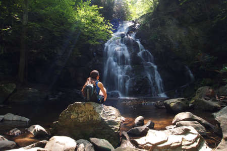 Young woman enjoying Spruce Flats Falls in the Great Smoky Mountains National Park, Tennessee, in early summer. Фото со стока