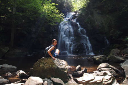 Young woman enjoying Spruce Flats Falls in the Great Smoky Mountains National Park, Tennessee, in early summer.