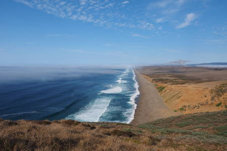 Waves breaking on the beach at Point Reyes National Seashore in Northern California, with fog beginning to roll in from the Pacific Ocean. Stock Photo