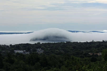 Dense fog rolling into Bar Harbor, Maine, covering islands in the distance in Frenchman Bay.