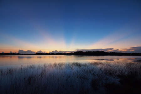 Sunrise with distinct sun rays over Nine Mile Pond in Everglades National Park, Florida.