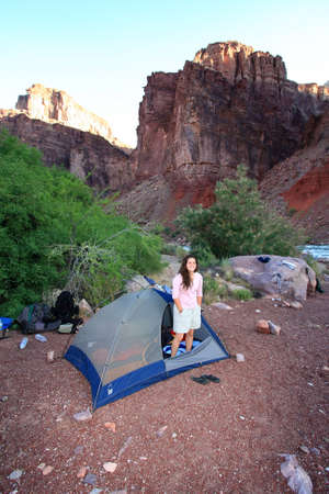 Young woman backpacker in her tent at the Hance Rapids campsite in Grand Canyon National Park, Arizona. Imagens