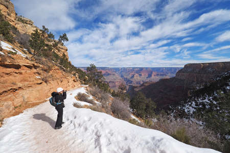 Woman hiking on a snowy Bright Angel Trail in Grand Canyon National Park, Arizona, in winter.