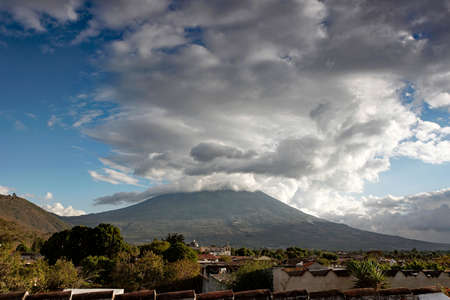 The Agua Volcano, a prominent stratovolcano visible throughout the city of Antigua in southern Guatemala, under a dramatic cloudscape.