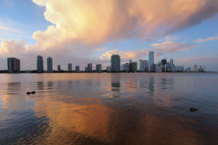 A very colorful cloudscape over the City of Miami skyline reflected on the calm waters of Biscayne Bay, Florida.