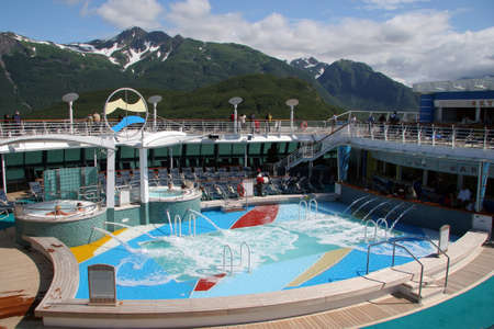 Yakutat Bay, Alaska - August 1, 2006 - Pool area of cruise liner with mountains of Yakutat Bay in the background. 版權商用圖片 - 133369442