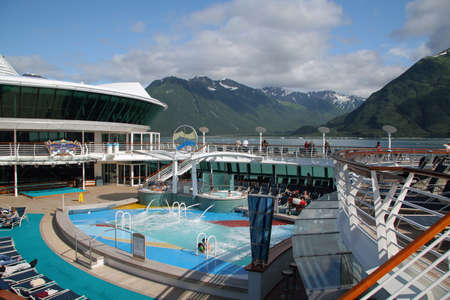Yakutat Bay, Alaska - August 1, 2006 - Pool area of cruise liner with mountains of Yakutat Bay in the background. 版權商用圖片 - 133369433