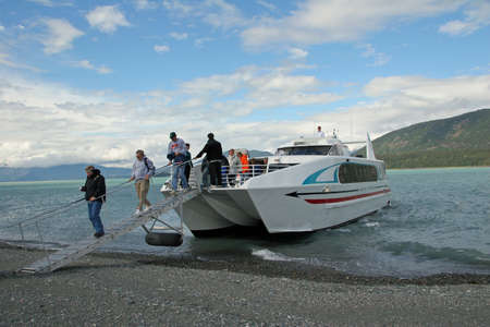 Glacier Point, Alaska - August 2, 2006 - Tourists disembark from catamaran on beach at Glacier Point on shore excurrsion during Inside Passage cruise. 新聞圖片