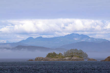 Rocky Islands in Alaskas Inside Passage on a sunny, hazy afternoon with mountains and clouds in the background. Stok Fotoğraf