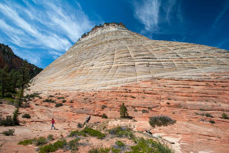 Young girl climbing on Checkerboard Mesa on the Zion Plateau, Utah on a summer morning under a beautiful cloudscape.