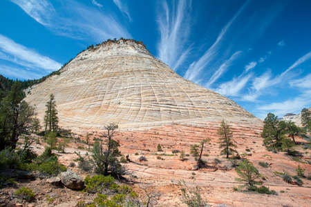 Checkerboard Mesa on the Zion Plateau, Utah on a summer morning under dramatic cloudscape.