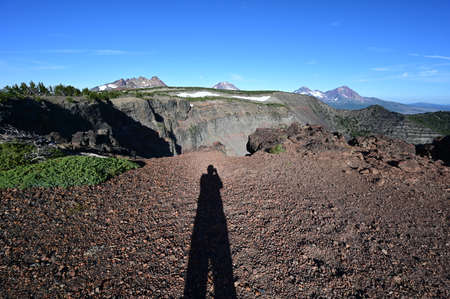 Photographers shadow in early morning light at end of Tam McArthur Rim Trail in Three Sisters Wilderness, Oregon.