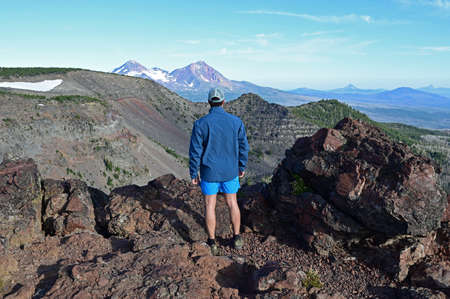 Young male trail runner enjoys view of Three Sisters volcanoes at end of Tam McArthur Trail in Three Sisters Wilderness, Oregon.