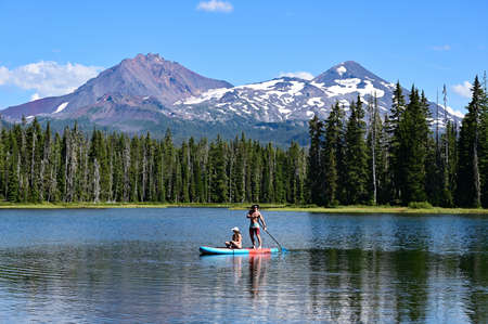 Young couple paddle boarding on Scott Lake, Oregon, with Middle and North Sisters volcanoes in the background on a calm sunny summer afternoon. Banco de Imagens