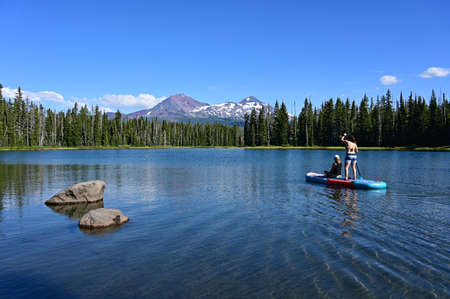 Two young women on standup paddle board on Scott Lake, Oregon with Middle and North Sisters volcanoes in background.