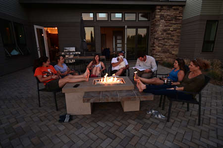 Sisters, Oregon - August 14, 2019 - Family and friends enjoy afternoon around fire pit in Sisters, Oregon on a clear summer afternoon.