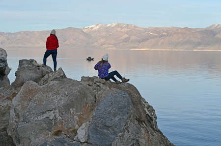 Two young women enjoy view of tranquil Pyramid Lake, Nevada from rock formation on coast on clear cool winter afternoon. Stock Photo