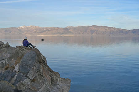 Young woman in blue sweater enjoys view of tranquil Pyramid Lake, Nevada from rock formation on coast on a calm clear winter afternoon. Stock Photo