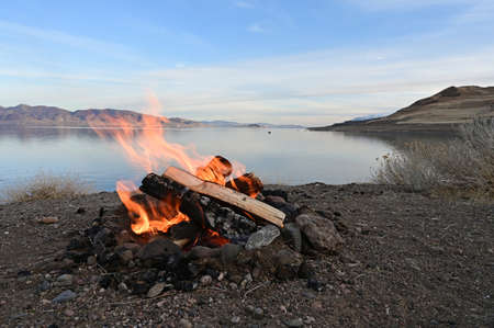 Campfire on rock formation overlooking Pyramid Lake, Nevada with lake in background on tranquil late winter afternoon.