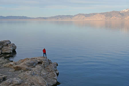 Young woman in red sweater and jeans enjoying view of Pyramid Lake, Nevada from rock formations on coast on late winter afternoon. Stock Photo