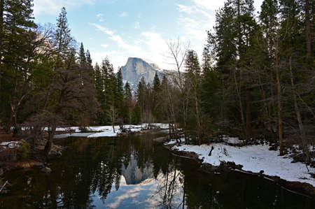 Half Dome and surrounding woods reflected in Merced River in Yosemite National Park, California under winter cloudscape. Stock Photo