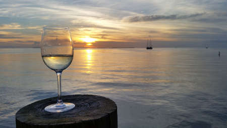 Wine glass on dock post at sunset in Islamorada, Florida with tranquil Florida Bay in background. Reklamní fotografie